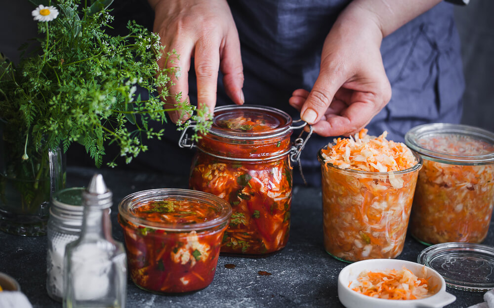 Person pickling fermented foods at home.